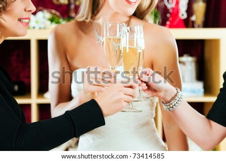 Bride at the clothes shop for wedding dresses; she is choosing a dress and is clinking glasses with her friends