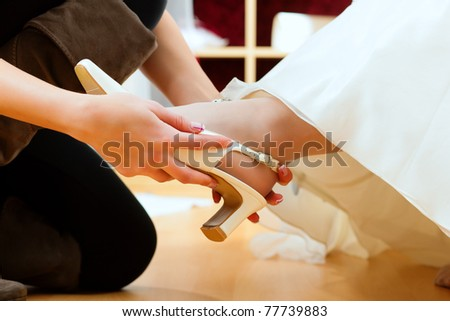 Bride at the clothes shop for wedding dresses; she is choosing a dress is fitting bridal shoes