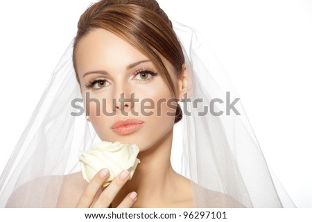 Bride beauty close up / Beautiful young brunette woman in a wedding dress with veil holding white rose