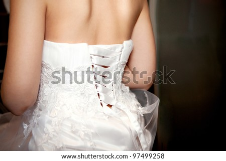 Bride being laced into a wedding dress