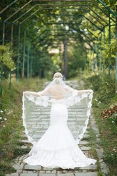 Bride blonde in a white chic wedding dress holding a small fish in her hands holding a long veil with a cherry and looks into the distance at a path leading up in the forest. Vertical photo, back