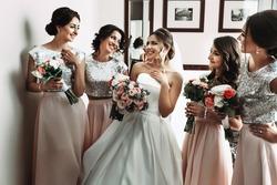 Bride & bridesmaids posing with bouquets in hotel room
