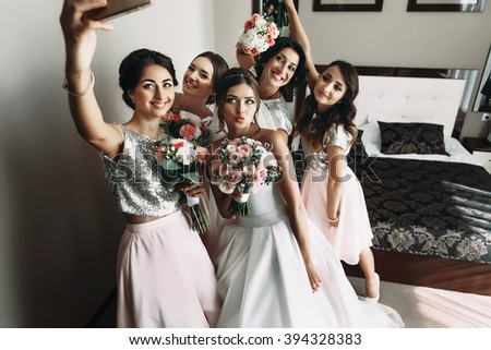 Bride & bridesmaids posing with bouquets, taking selfie