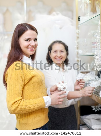 bride chooses bridal accessories at wedding store. Consultant helps her