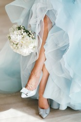 Bride dresses shoes before the wedding ceremony. bride morning. Closeup detail of bride putting on high heeled sandal wedding shoes. Blue Dresses
