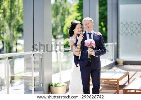 bride embraces the groom\'s shoulder. The bride with a wedding bouquet of orchids
