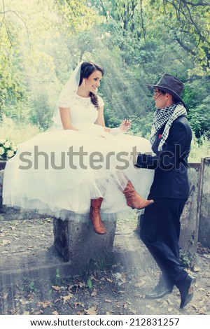 bride flirting with the groom in a cowboy hat
