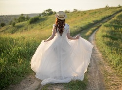 Bride from the back in a wedding dress walking on sunset in the field