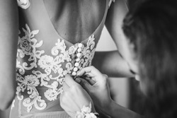 Bride getting dress up by a bridesmaid