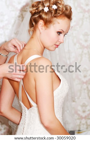 Bride getting ready before the ceremony. Focus on bridesmaid's left hand. - stock photo