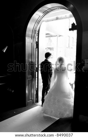 bride & groom walk toward the church door - stock photo