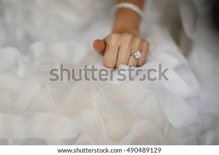 Bride hand with beautiful diamond ring on white dress
