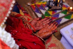 Bride hands with red henna pattern or design in Indian wedding or hindu tradition