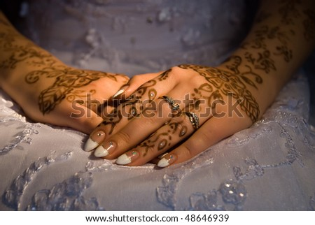 stock photo Bride hands with rings and tattoo on a wedding dress
