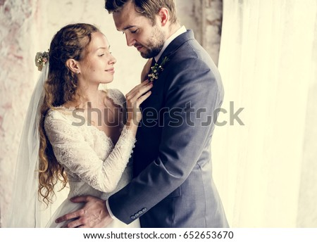 Bride Helping Groom Dressing Up for Wedding Ceremony #652653670