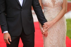 Bride hold groom's hand on red carpet