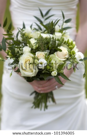 bride holding a bouquet of flowers with roses