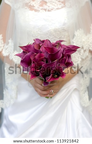 bride holding a bouquet of purple lily flowers