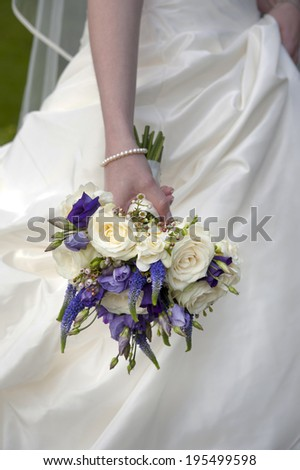 bride holding a purple and white wedding bouquet
