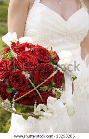 bride holding a red rose bouquet close up