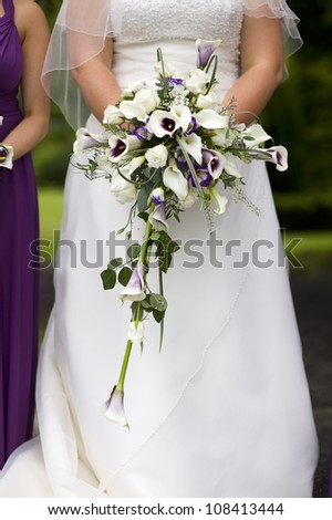 bride holding a wedding bouquet of purple and white roses and lilies