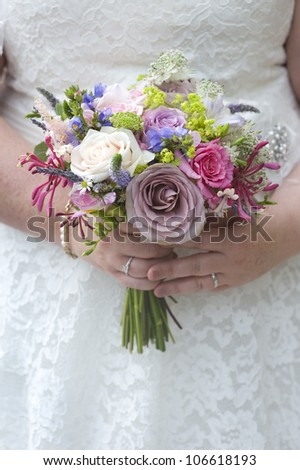 bride holding a wedding bouquet of roses and other flowers