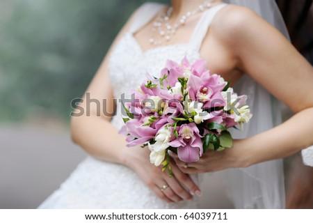 Bride holding beautiful pink wedding flowers bouquet