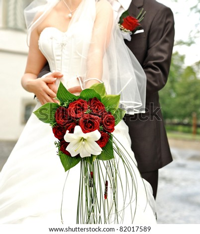 bride holding beautiful red roses. wedding flowers bouquet. selective focus
