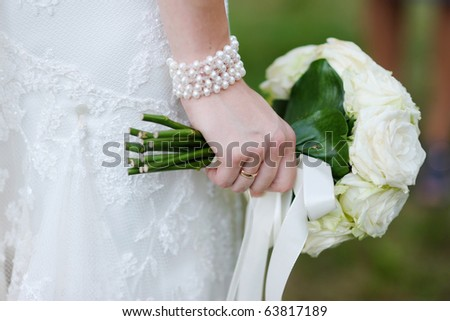 Bride holding beautiful white wedding flowers bouquet