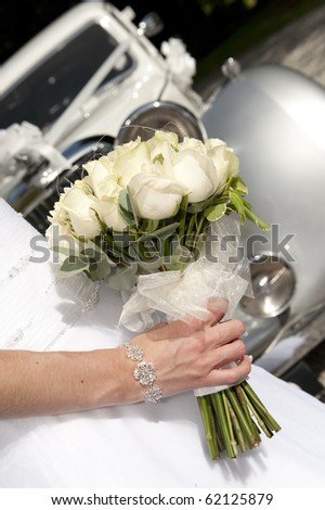 Bride holding bouquet in front of vintage wedding car - stock photo