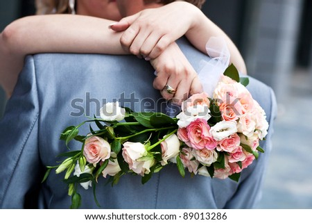 Bride holding bridal bouquet and groom hugging