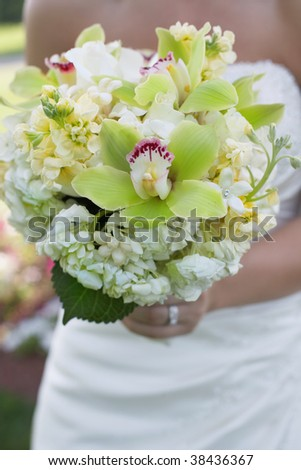 Bride holding colorful wedding bouquet against dress