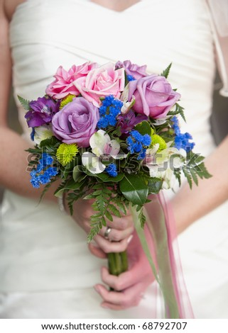 Bride holding colorful wedding bouquet in hands