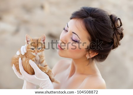 Bride holding ginger kitten in hands