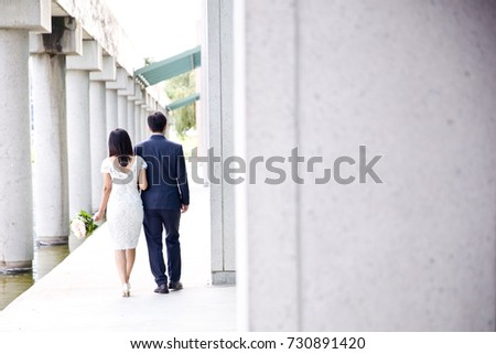 Bride holding on to the arm of the groom as they go for a walk