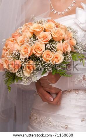 Bride holding orange bouquet detail