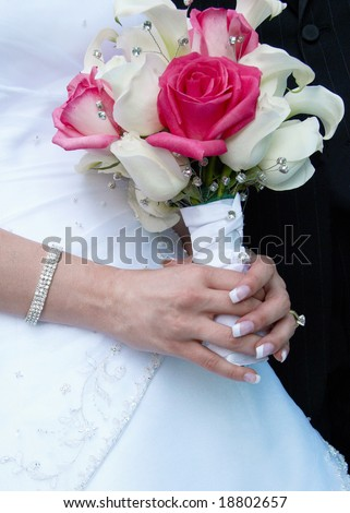 stock photo Bride holding pink and white wedding bouquet against gown