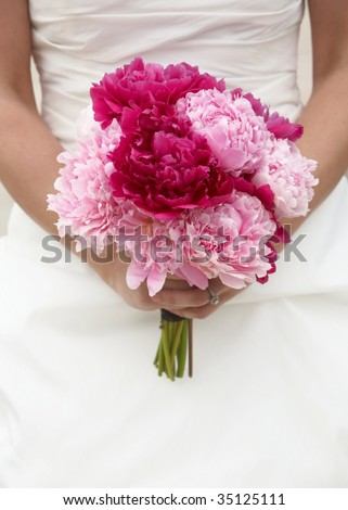 Bride holding red and pink wedding bouquet against gown - stock photo