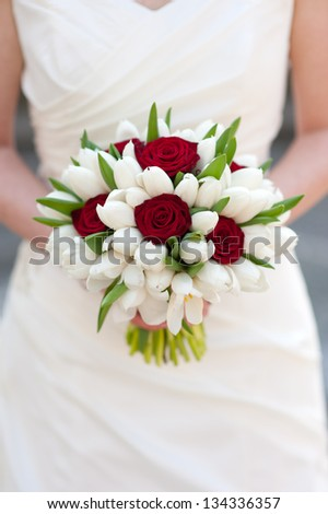 bride holding red rose and white tulip wedding bouquet