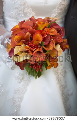 stock photo Bride holding wedding bouquet of calla lilies against dress