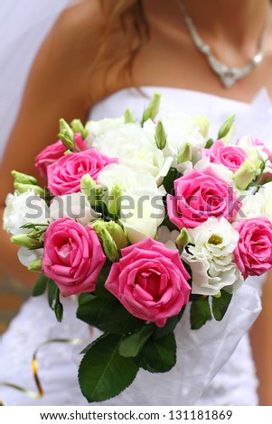 Bride holding wedding bouquet of pink and white roses close up