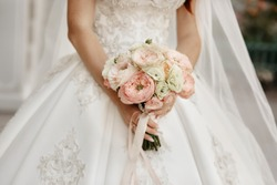 Bride holding wedding bouquet. Pink gold and ivory style