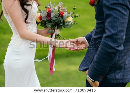 Bride holding wedding bouquet with groom on the green background #718098415
