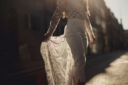 bride holding wedding trouser dress in light