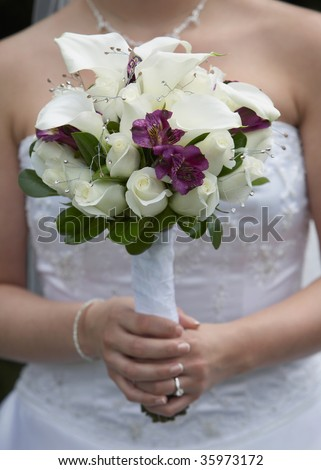 stock photo Bride holding white and purple wedding bouquet against gown
