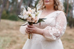 bride holds a wedding bouquet of white and beige flowers outdoors. original festive  bouquet  in woman hands. stylish wedding bouquet of white and pink flowers. wedding decor. wedding day