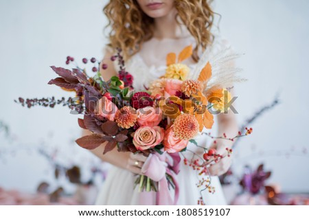 Bride holds beautiful autumn bouquet with orange and red flowers and berries. Autumn bouquet with ribbons in bride's hands Foto stock ©