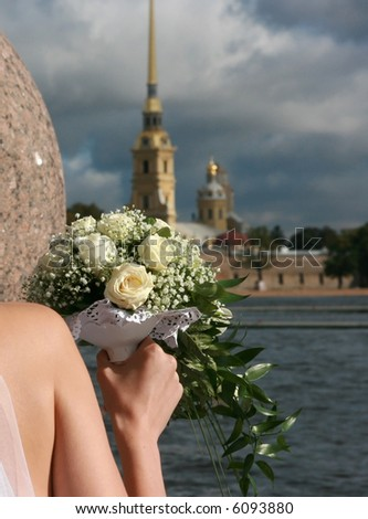 Bride holds bouquet of white roses. The Peter and Paul Fortress. St. Petersburg. Russia.