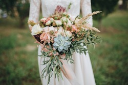 bride in a dress standing in a green garden and holding a wedding bouquet of flowers and greenery