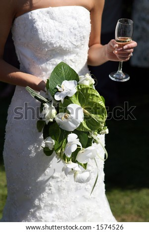 Bride in a white wedding dress holding a beautiful bouquet of flowers and a glass of alcohol